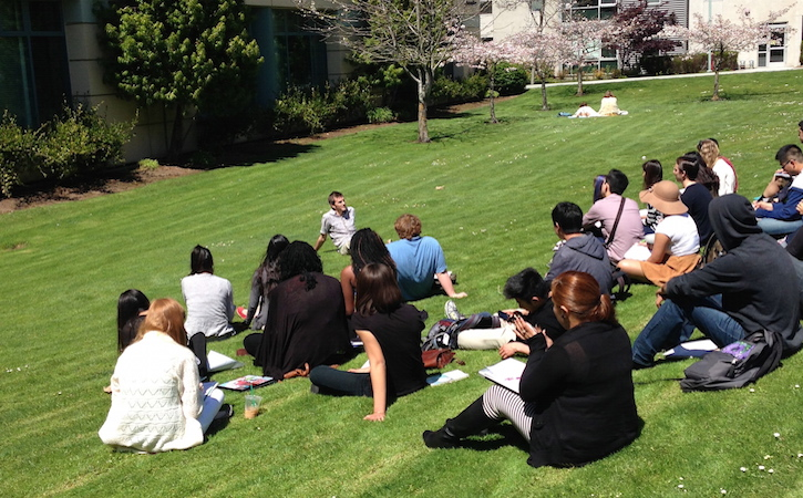 Philosophy students sitting on grass on campus